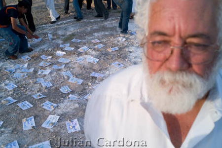 Man with white beard and hair in front of camera with papers scattered on floor in background