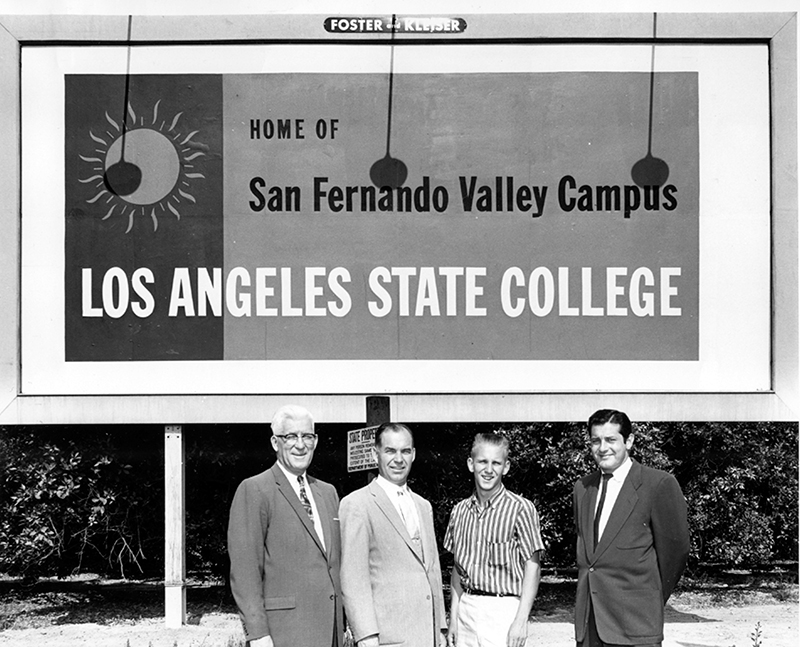 Four men standing in front of a sign