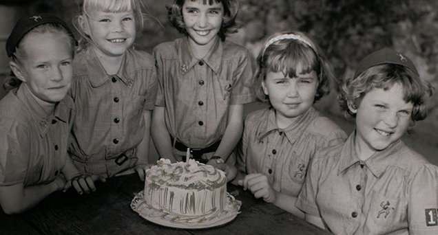 Five young girls around a table looking at the camera with a cake in the center