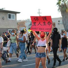 Masked woman marching with others, carrying a sign with English and Chinese: PROTECT BLACK LIVES!