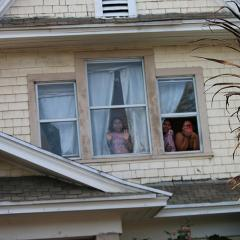 People watch from the second-story windows of a house