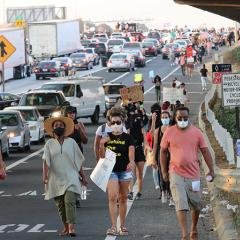 Four masked people leading others in a march along the freeway