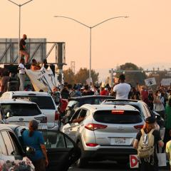 Cars and protesters clustered on the freeway, some people standing on cars