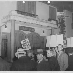 Photograph of people protesting in front of a German house