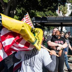 White man holds a black woman with her arms pinned.  Man in a  Qanon shirt, with American and Don't Tread on Me flags in the foreground