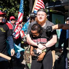White man holds a black woman with her arms pinned while she is sprayed with mace directly in her eyes, others with Trump campaign and Stop the Steal gear look on