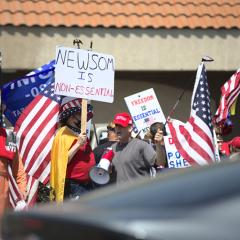 People standing with American flags and signs: NEWSOM IS NON-ESSENTIAL