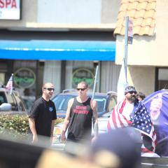 Three men standing on the street, won with a Silent Majority shirt, another with the American flag draped over his shouldersl; Trump banner on the car behind