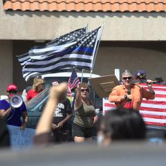 Group of people, one with a megaphone, others waving an American flag and altered American (blue line) flags.
