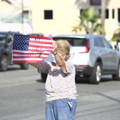 """Woman waves American flag with the message """"All Lives Matter"""""""