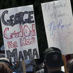 Two signs:  GEORGE Cried Out FOR HIS MAMA; No Justice, No Peace… No Racist Police