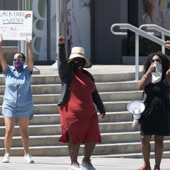 Three women with faces covered stand in protest, two with raised fists and one holding a handmade Black Lives Matter sign