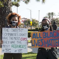 Two women in Black Lives Matter masks holding handmade signs: (1) THE SAFEST COMMUNITIES DON'T HAVE THE MOST COPS.  THEY HAVE THE MOST RESOURCES. #DEFUNDTHEPOLICE #CARENOTCOPS (2) ALL BLACK LIVES MATTER