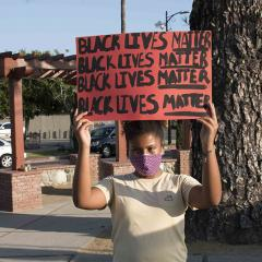 Woman in mask holding a handmade sign with  BLACK LIVES MATTER written four times.