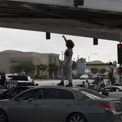 Protesters standing on top of cars in a street procession