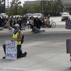 Two masked protesters kneel in the street with handmade signs: (1) IS THERE WHITE SUPREMACY IN YOUR FAMILY? (2) FUCK THE POLICE (3) PROSECUTE KILLER COPS