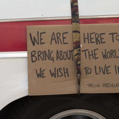 Cardboard sign strapped to a vehicle: WE ARE HERE TO BRING ABOUT THE WORLD WE WISH TO LIVE IN -- MELINA ABDULLAH