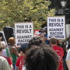 Crowd of protesters with two signs: THIS IS A REVOLT AGAINST RACISM
