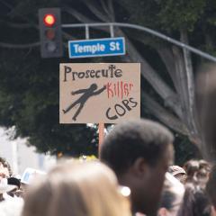 Cardboard sign: Prosecute Killer COPS