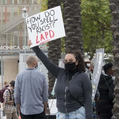Masked woman holding handmade sign: HOW DO YOU SPELL RACIST? LAPD
