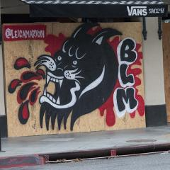 BLM and panther mural painted over a boarded storefront