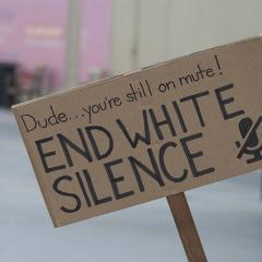 Cardboard sign: Dude…you're still on mute!  END WHITE SILENCE