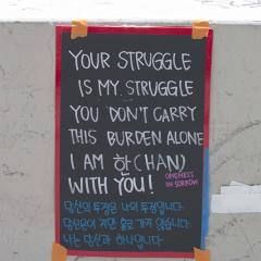 Sign in both English and Korean languages taped to a wall: YOUR STRUGGLE IS MY STRUGGLE.  YOU DON'T CARRY THIS BURDEN ALONE. I AM WITH YOU