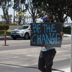 Masked protester holds a handmade sign: BE THE CHANGE