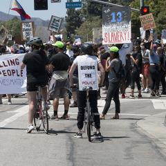 Large crowd of people in a street intersection with signs and banners that include: STOP KILLING BLACK PEOPLE; DEFUND THE POLICE; THE 13th Amendment LEGALIZES SLAVERY!; POLICE REFORM NOW; FUCK TRUMP; BLACK LIVES MATTER