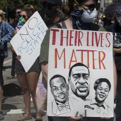 Two signs: NO POLICE STATE; THEIR LIVES MATTER (with drawings of two men and one woman)