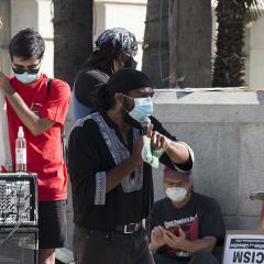 Masked speaker speaking through microphone