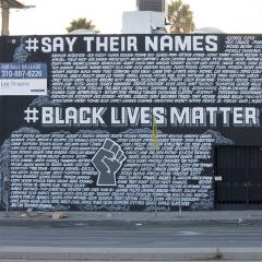 Side of a two-story building covered with a mural: JUSTICE 4, #SAY THER NAMES, #BLACK LIVES MATTER and many names.