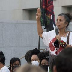 Woman holds up 3 fingers in right hand, microphone in left hand.