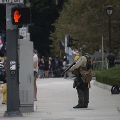 Armed officer standing on the sidewalk