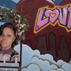 Shrine decorated with candles and flowers and a photo of Breonna Taylor, mural of Love in the background