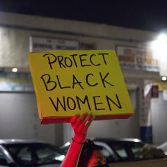 Hand holding handmade sign: PROTECT BLACK WOMEN