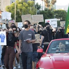 Masked protesters marching with an Ethiopian flag and signs:  BLM; NOTHING F*CKING MATTERS UNTIL BLACK LIVES MATTER; NO JUSTICE NO PEACE