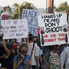 Masked marchers with signs: DEFUND THE POLICE; JUSTICE FOR BREONNA; A COP SHOT A BLACK WOMAN & WAS ONLY CHARGED FOR THE SHOTS MISSED!!!; BLACK LIVES MATTER!; HANDS UP MEANS DON'T SHOOT OR DID YOU FORGET THAT