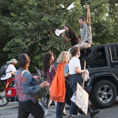 From the back of a moving Humvee, a woman speaks through megaphone, while a man beside her shouts with a raised fist.  Protesters follow behind.