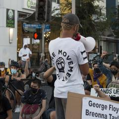 A speaker with a megaphone addresses a crowd kneeling in the street