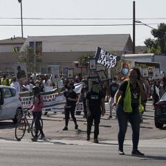 Masked marchers carrying signs including: BLACK LIVES MATTER