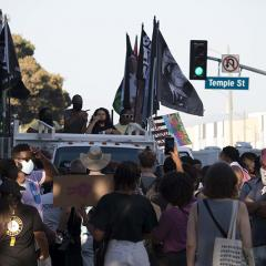 Group of masked people surrounding a vehicle carrying multiple flags include BLACK LIVES MATTER and a photo of Malcolm X