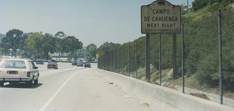 Cars driving along a road, next to road is a sign with a bear icon and the words 'Campo de Cahuenga Next Right'