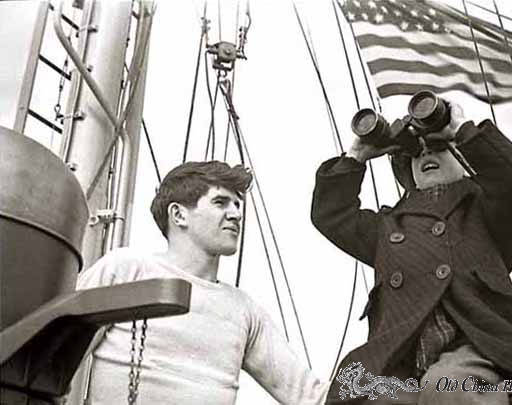 Boy looking through binoculars aboard a ship with man next to boy; US flag in the background